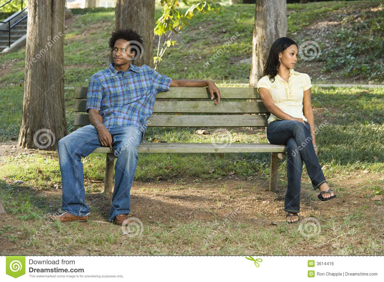 ... sitting on opposite sides of park bench looking away from eachother