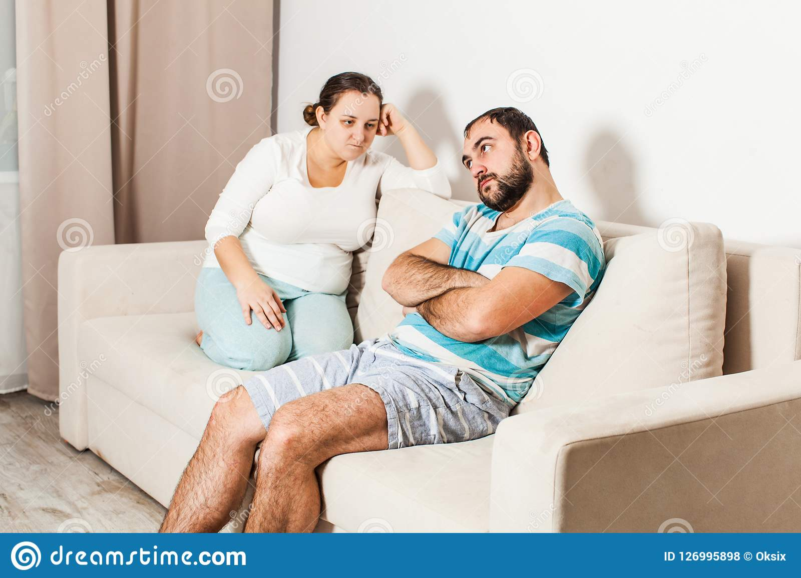 Couple sitting on couch at home in the living room.