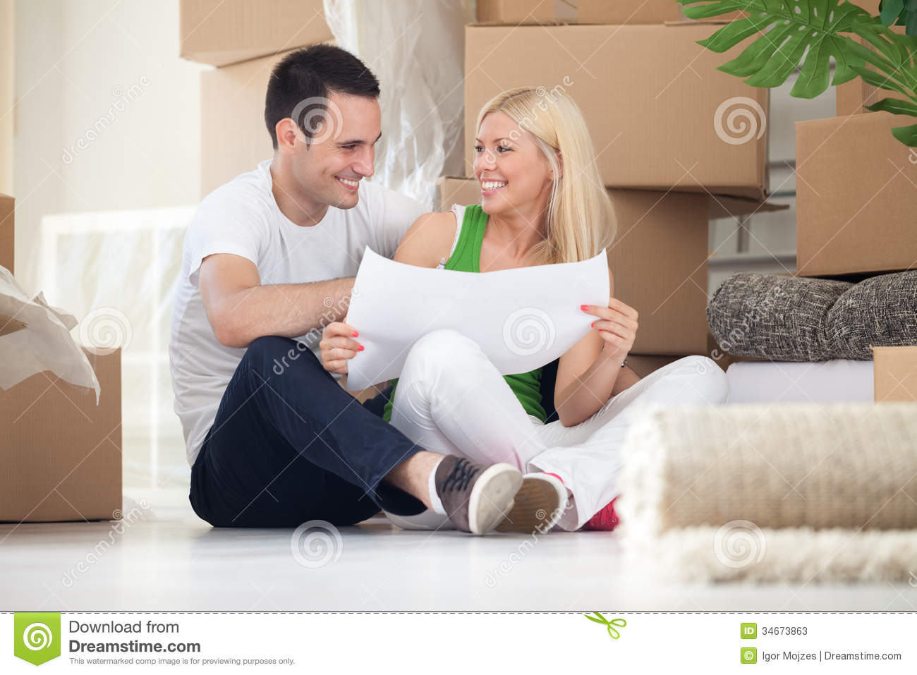 Couple Sitting On Floor Looking At House Plans Stock Photos    Couple sitting on floor looking at house plans