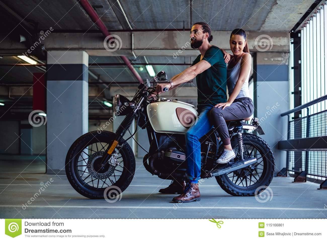Couple Sitting On A Motorcycle In A Garage Stock Image Image Of