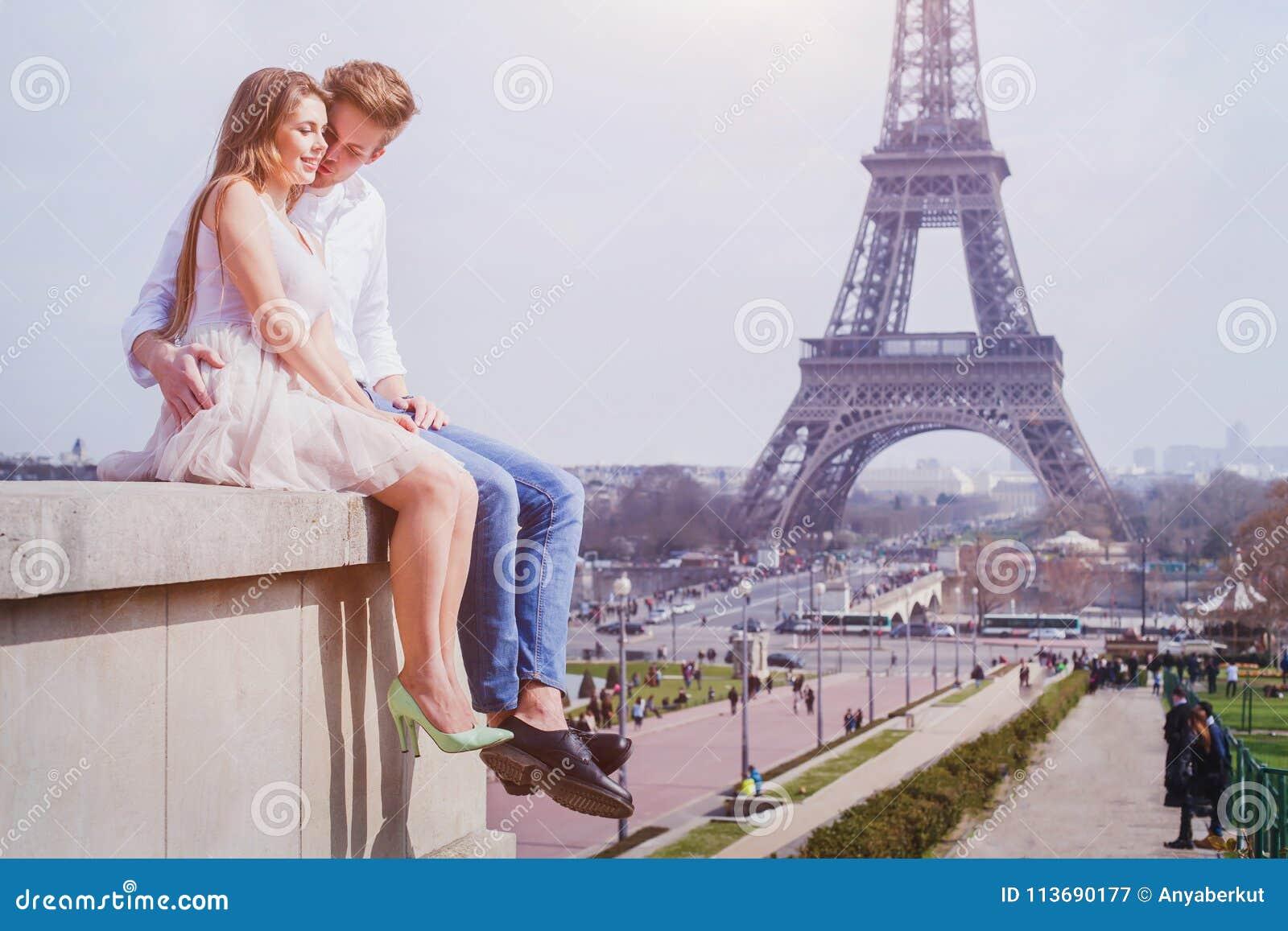 Couple sitting near Eiffel Tower in Paris, honeymoon in Europe