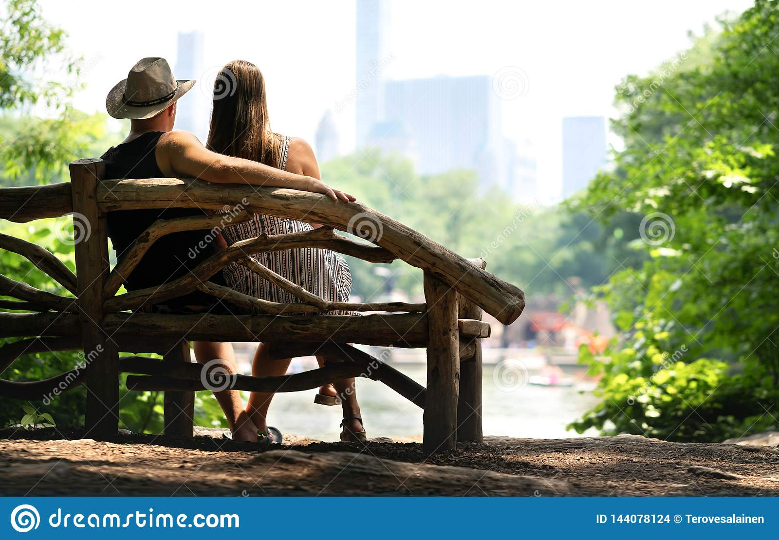 Couple sitting on a park bench and having a romantic first date. Lovers with romance and trust.