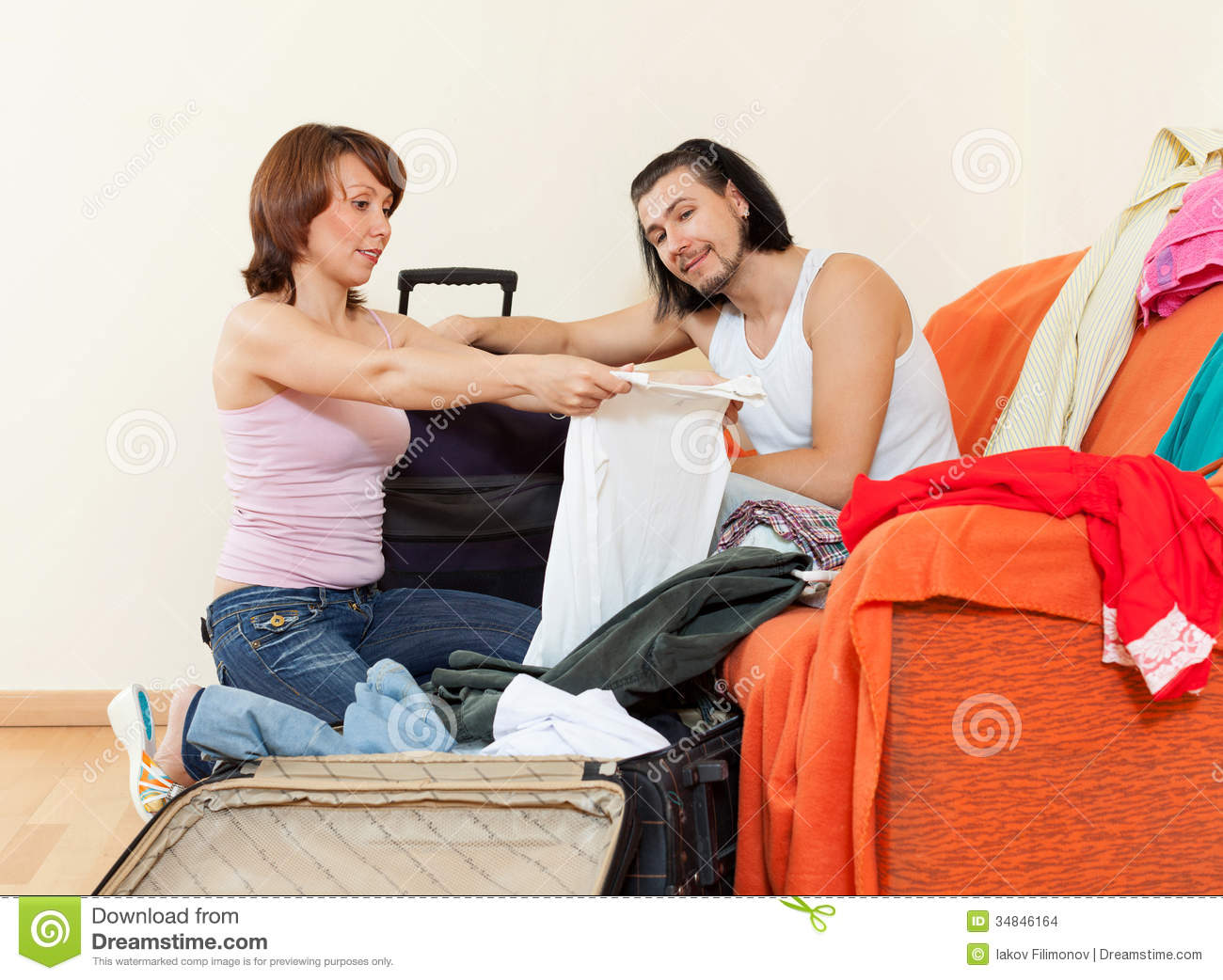 Couple Sitting On Sofa And Packing Suitcase At Home Stock