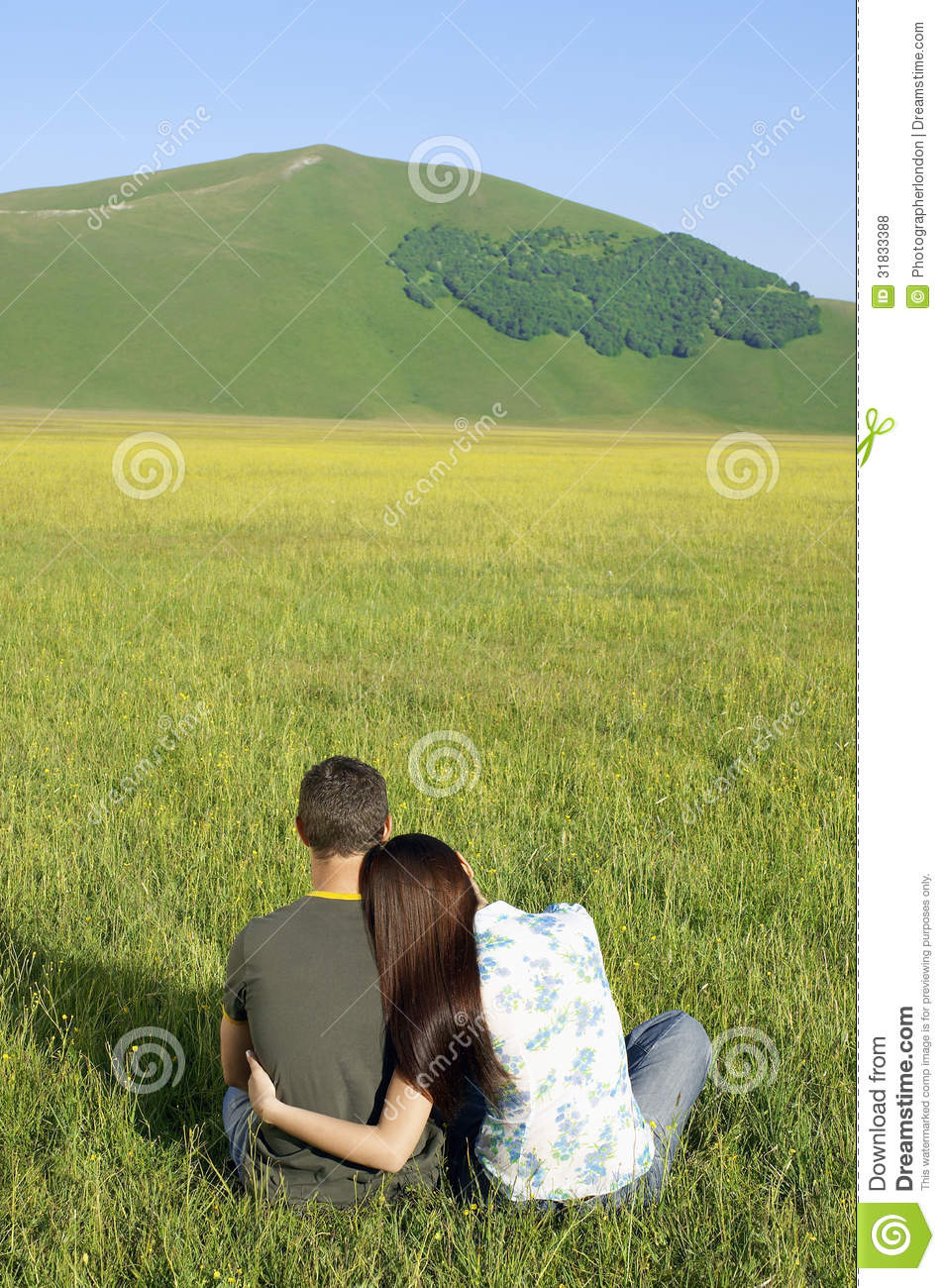 Couple Sitting Together On Grassy Field At Against ...
