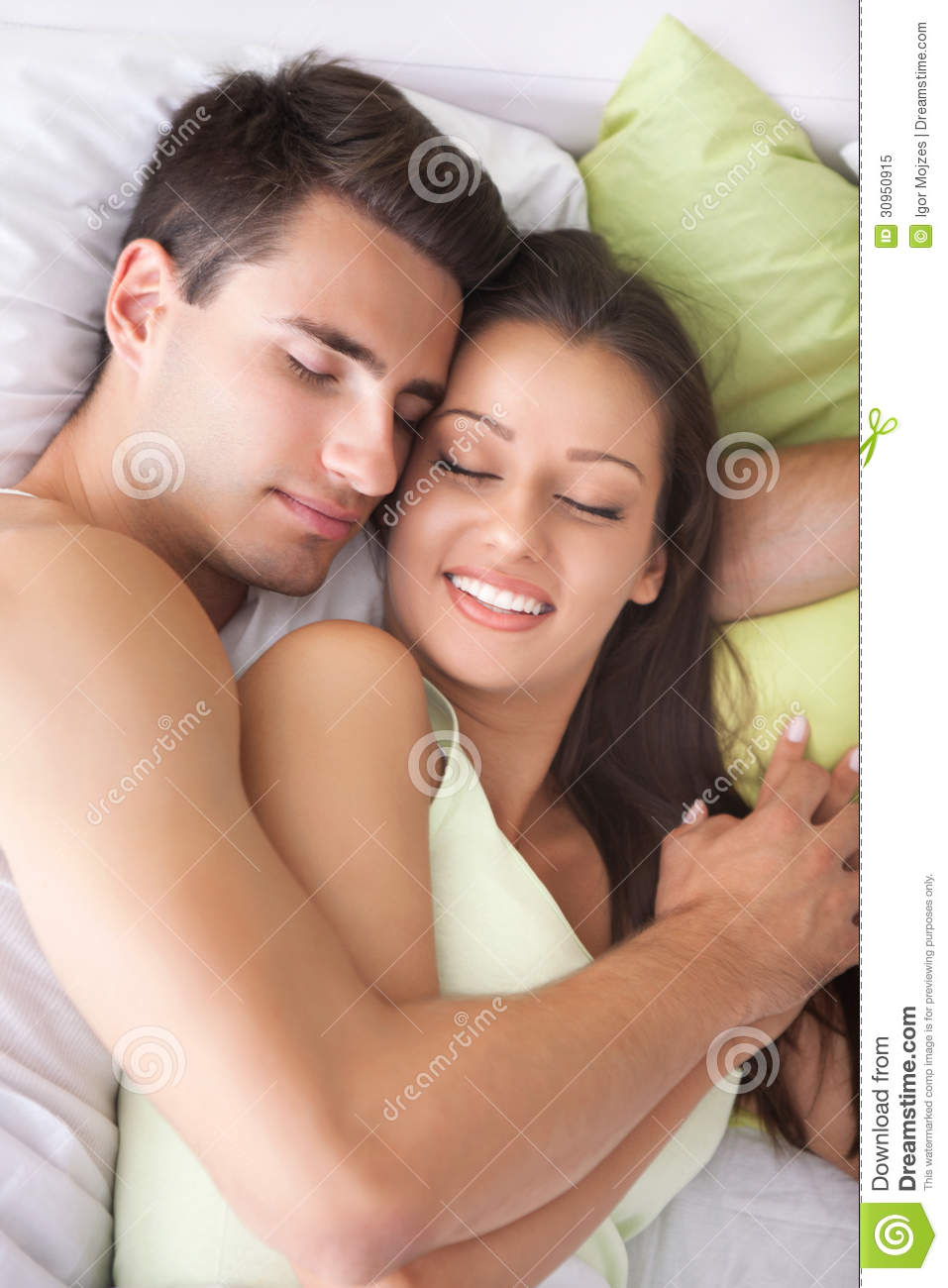 Young couple sleeping and hugging on the bed in bedroom.