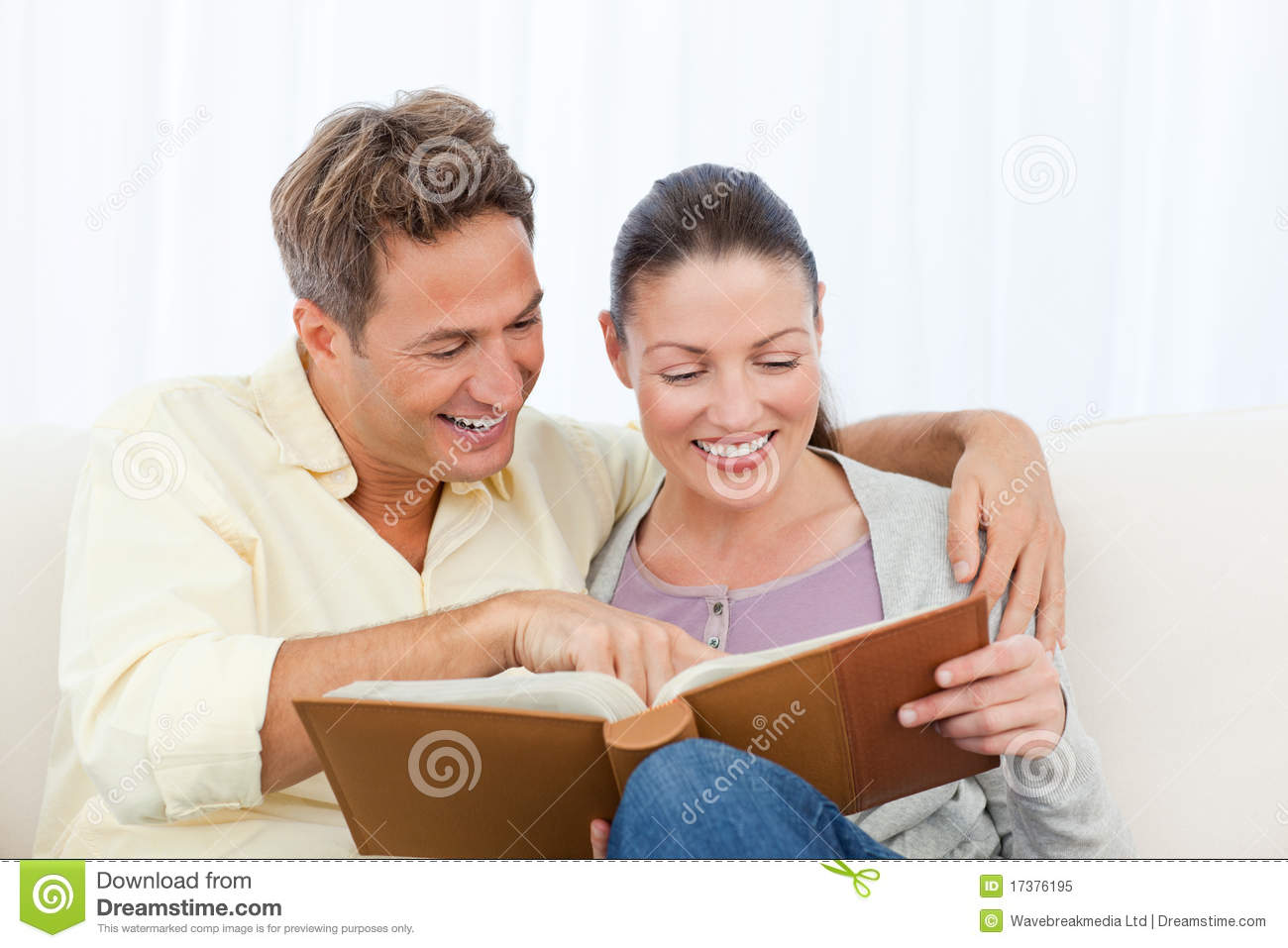 couple smiling while looking a photo album royalty free. Black Bedroom Furniture Sets. Home Design Ideas