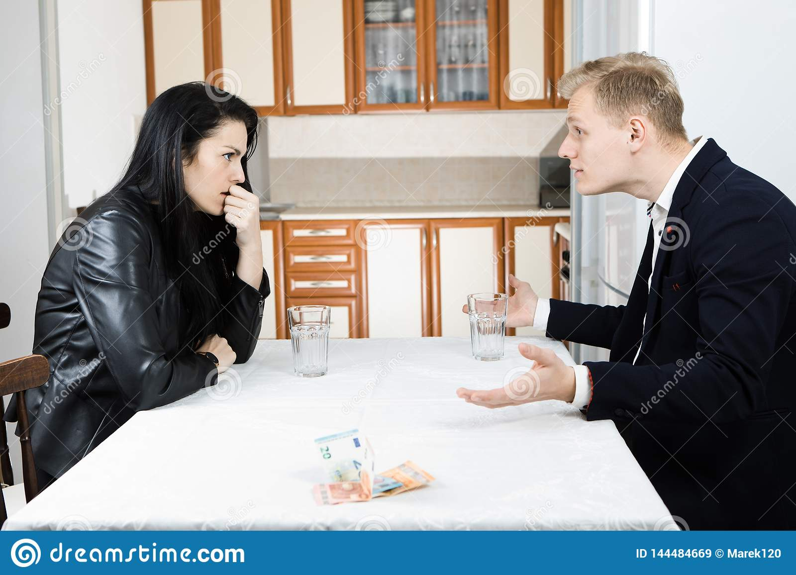 Couple solving financial crisis together on table in kitchen