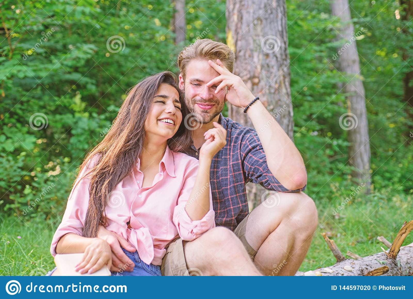 Couple spend time outdoors on sunny day. Youth on picnic or hike relaxing and having fun. Pleasant weekend. Couple