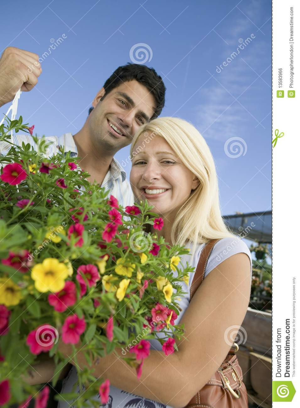 Couple standing in plant nursery