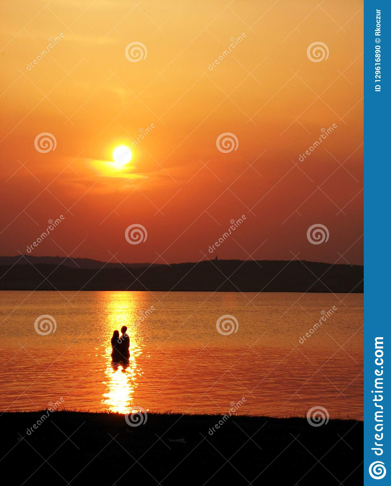 Couple standing in the water at sunset