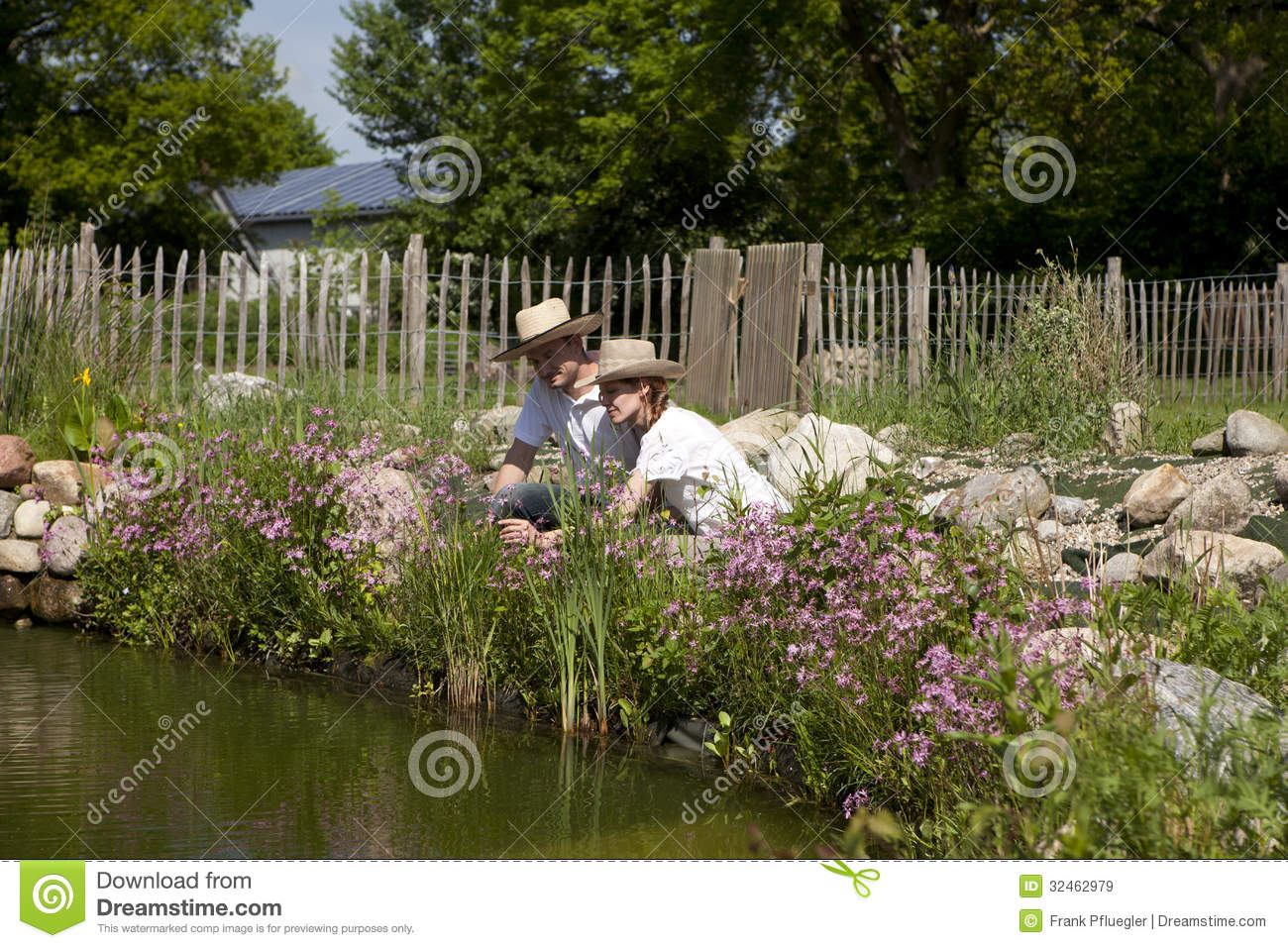 Couple with a straw hat on the garden pond royalty free for Garden pond unlimited