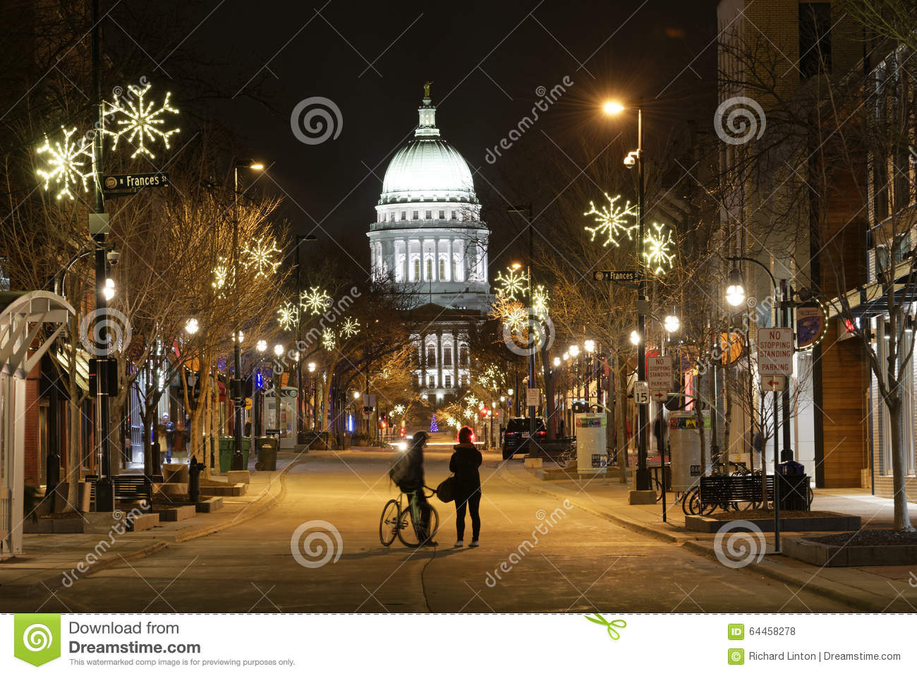Couple In Street Looking At Capitol On A Snowy Evening In