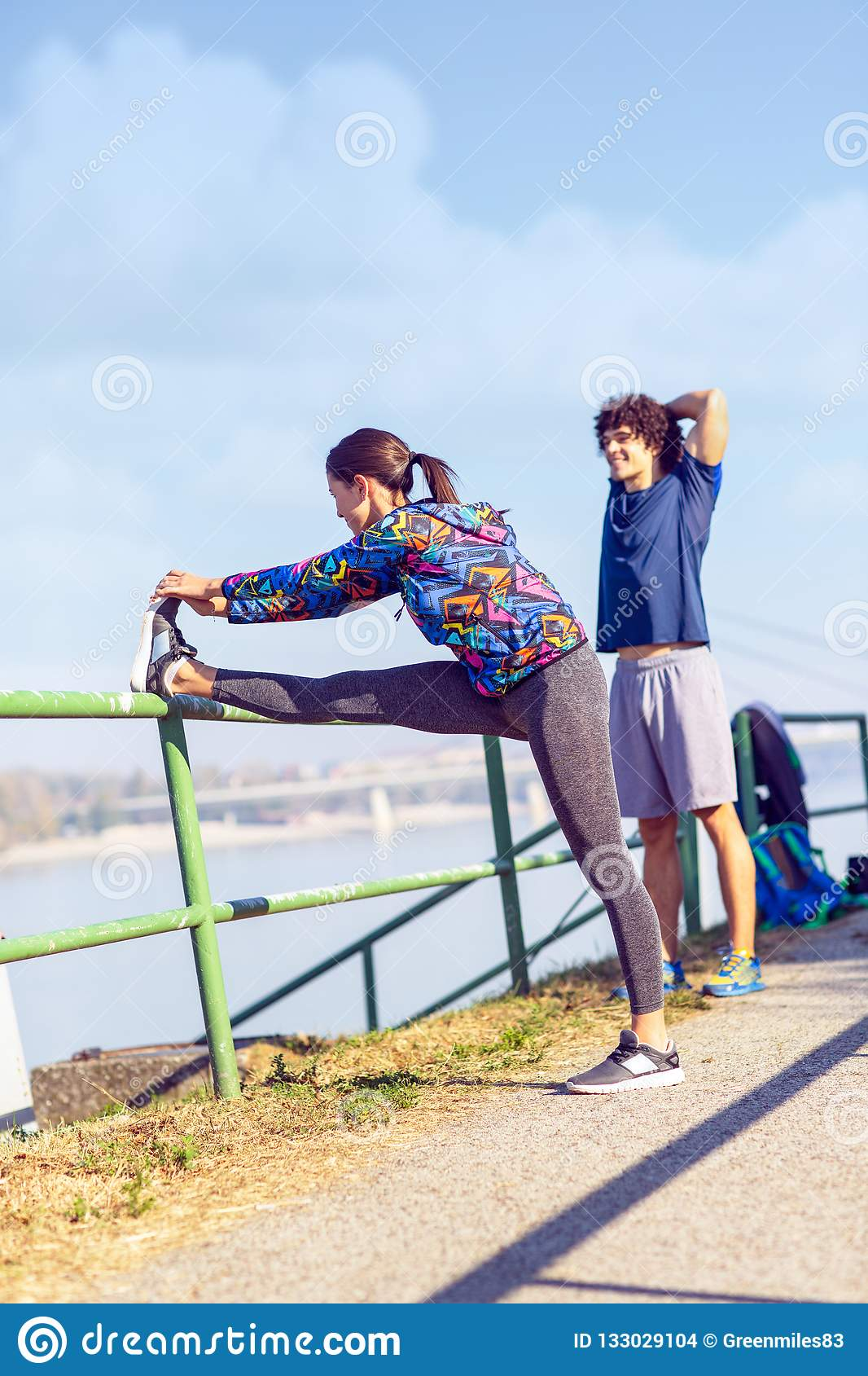 couple stretching outdoors - fitness, sport, training and lifestyle concept .