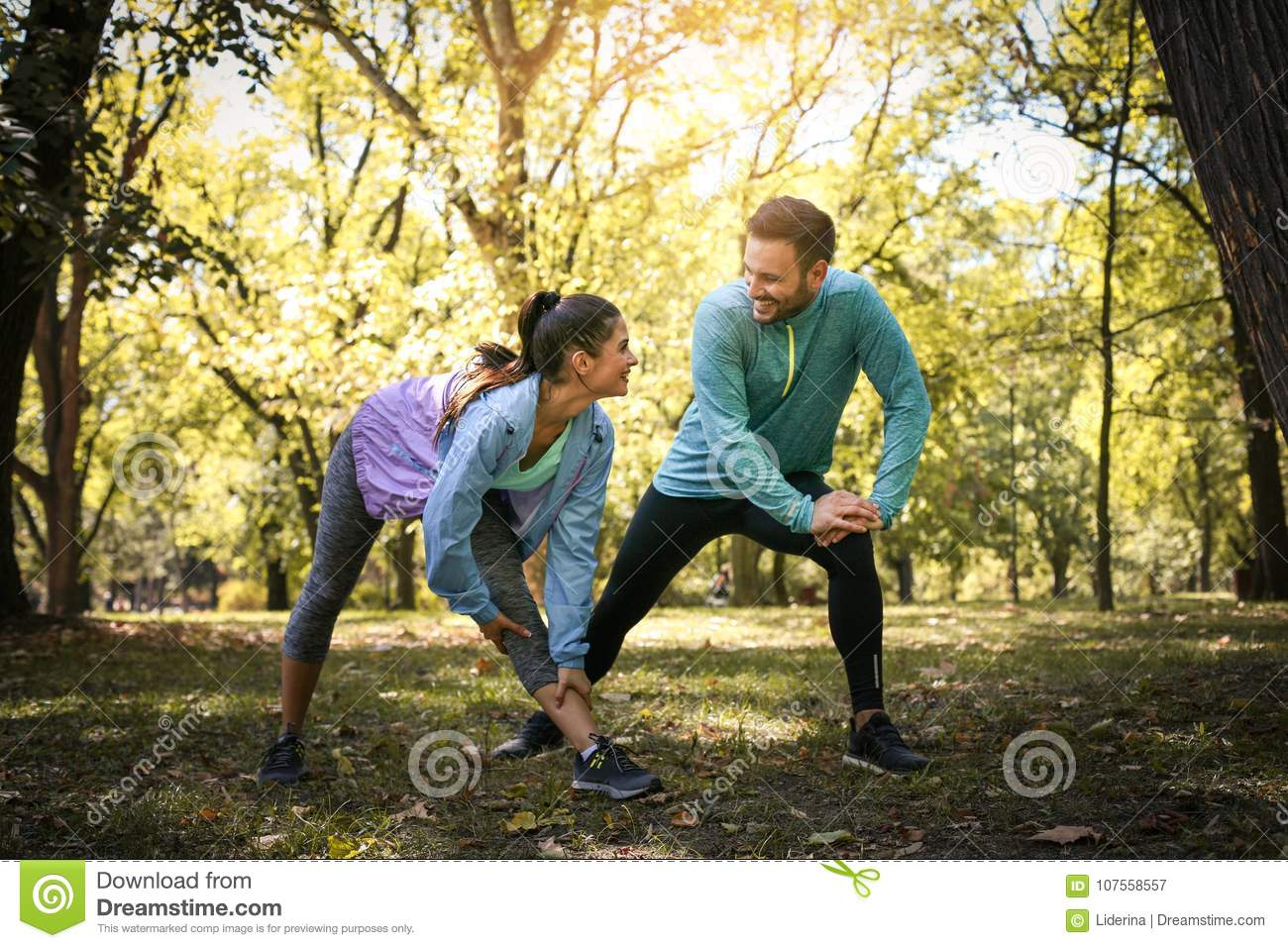 Couple stretching in park. Young couple working exercise togethe