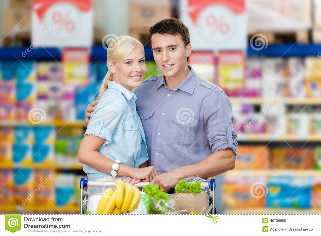Couple In The Supermarket With Cart Full Of Food Stock Photo