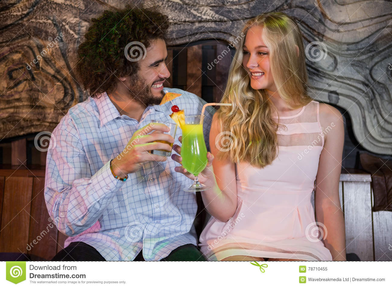 Couple toasting glass of cocktail in bar