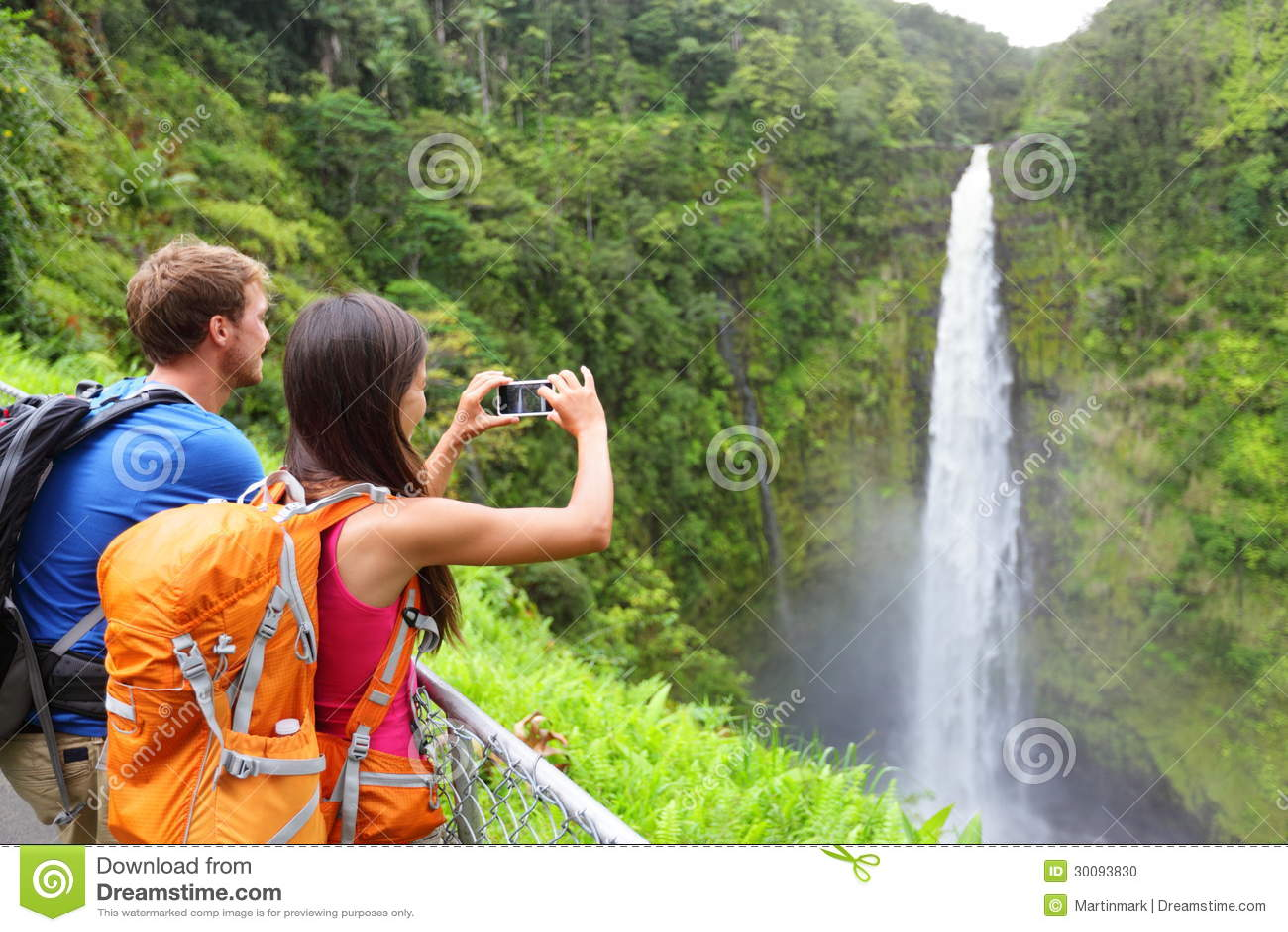 Couple tourists on Hawaii by waterfall