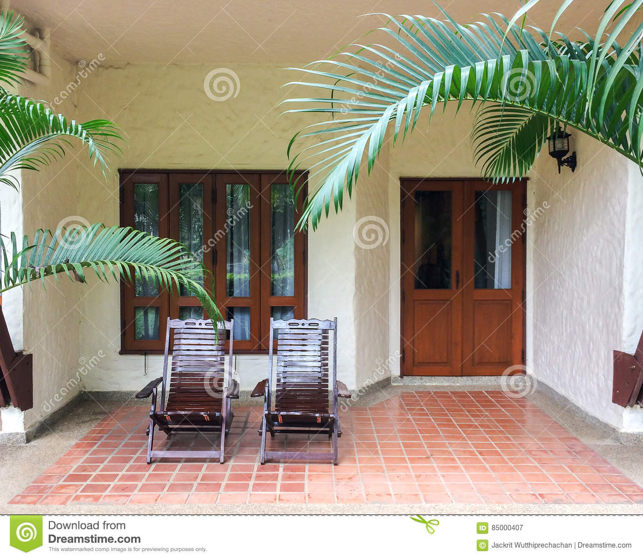 Couple of Traditional Wooden Deck Chairs on Patio of Balcony or Terrace in Open Area in front of Windows and Doors for Relax