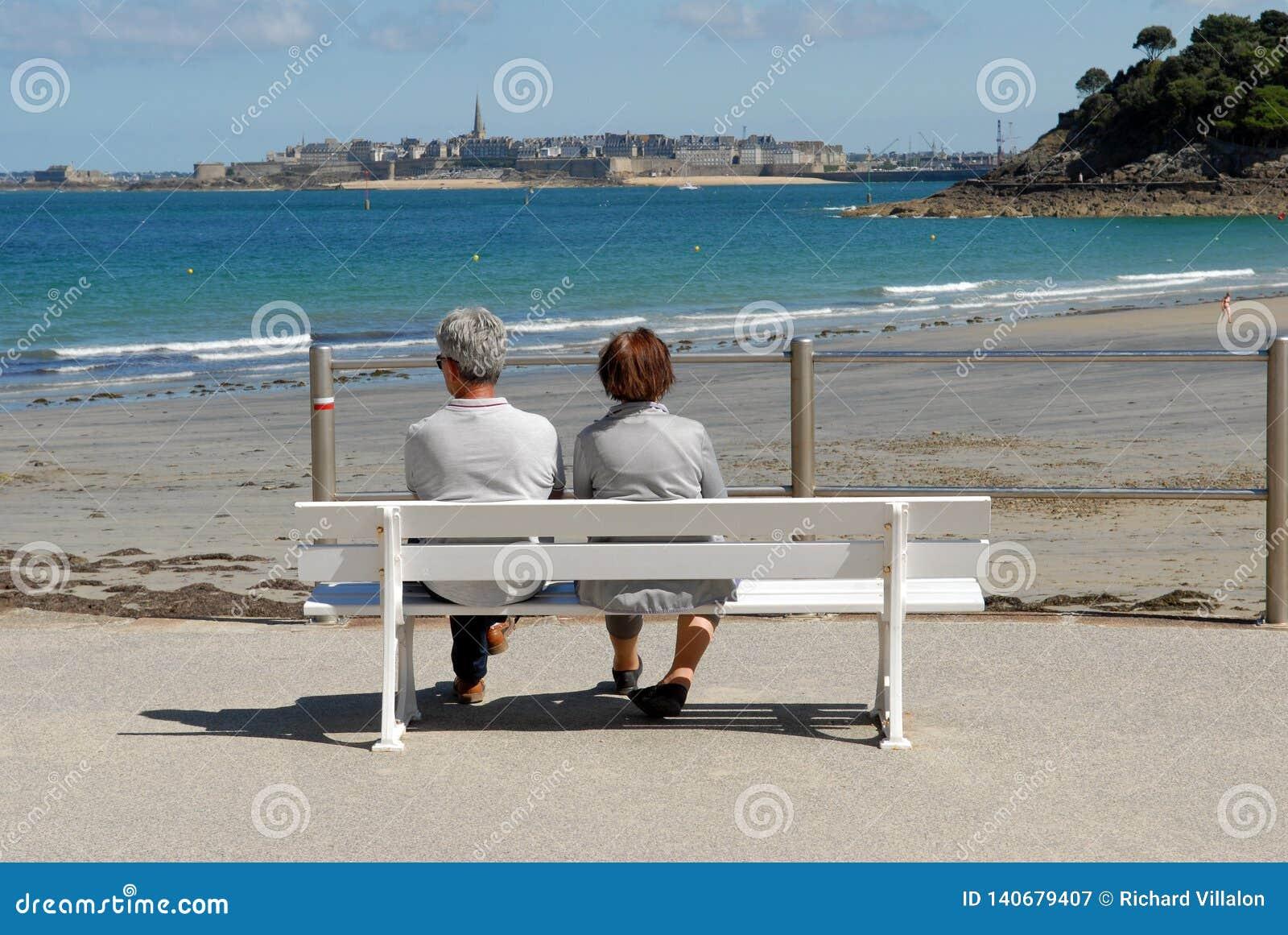 Couple on a bench facing Saint-Malo