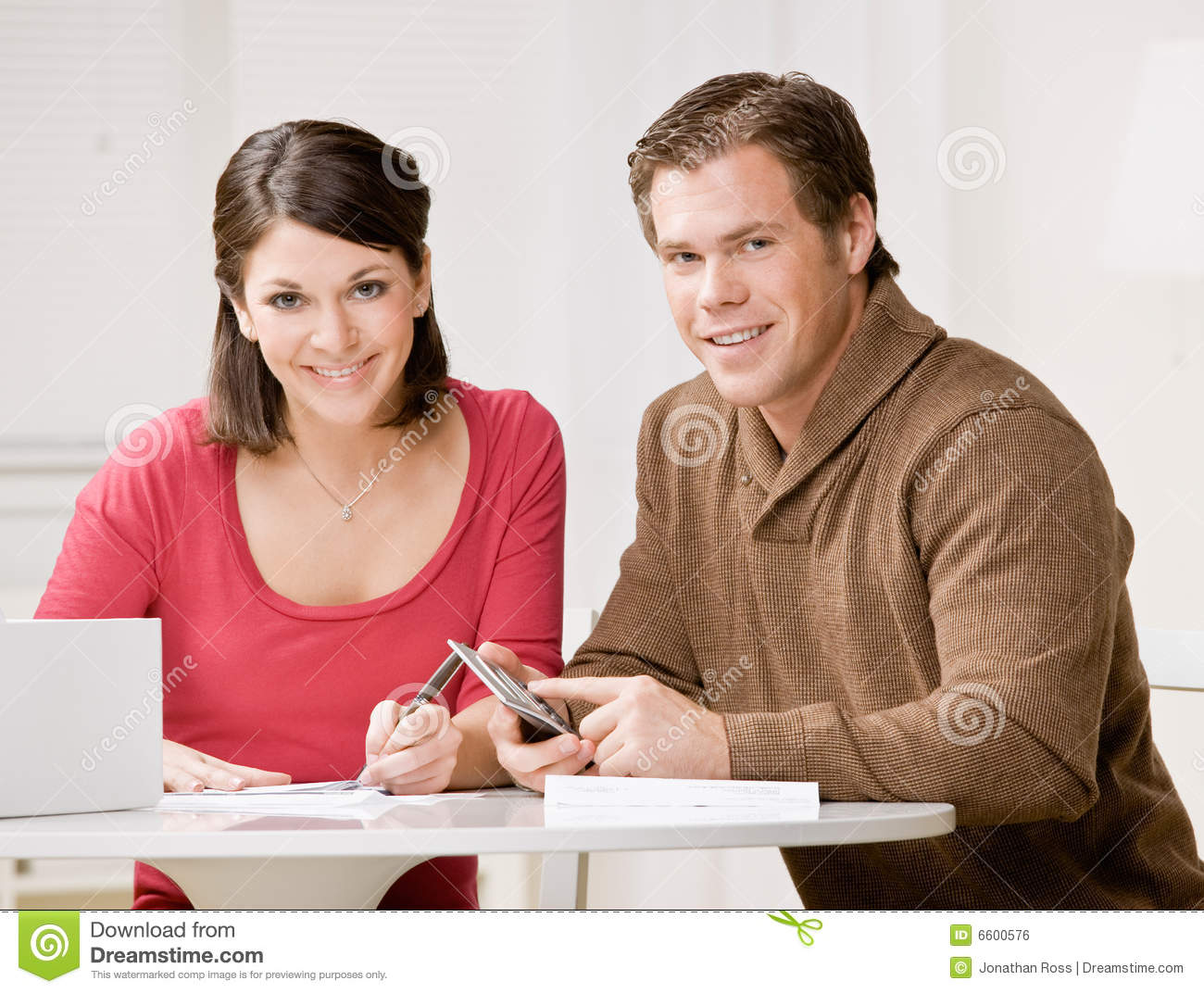 couple using calculator to pay monthly bills stock photo
