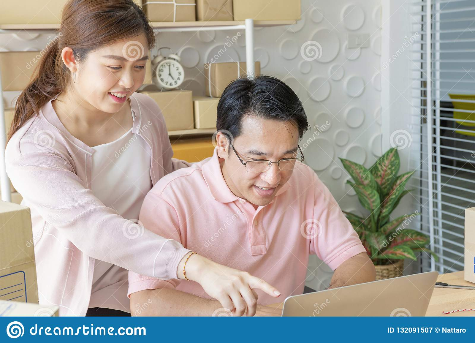 Couple using laptop at home. Pointing at screen with happily
