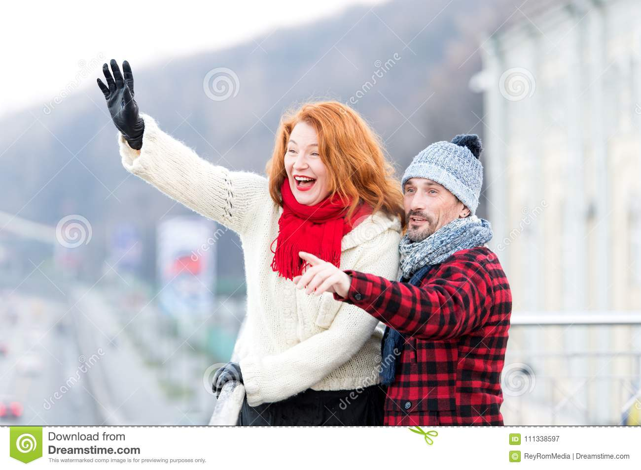 Couple wag to air. Red hair woman wag from the bridge. Happy lady with guy welcomes to friends.
