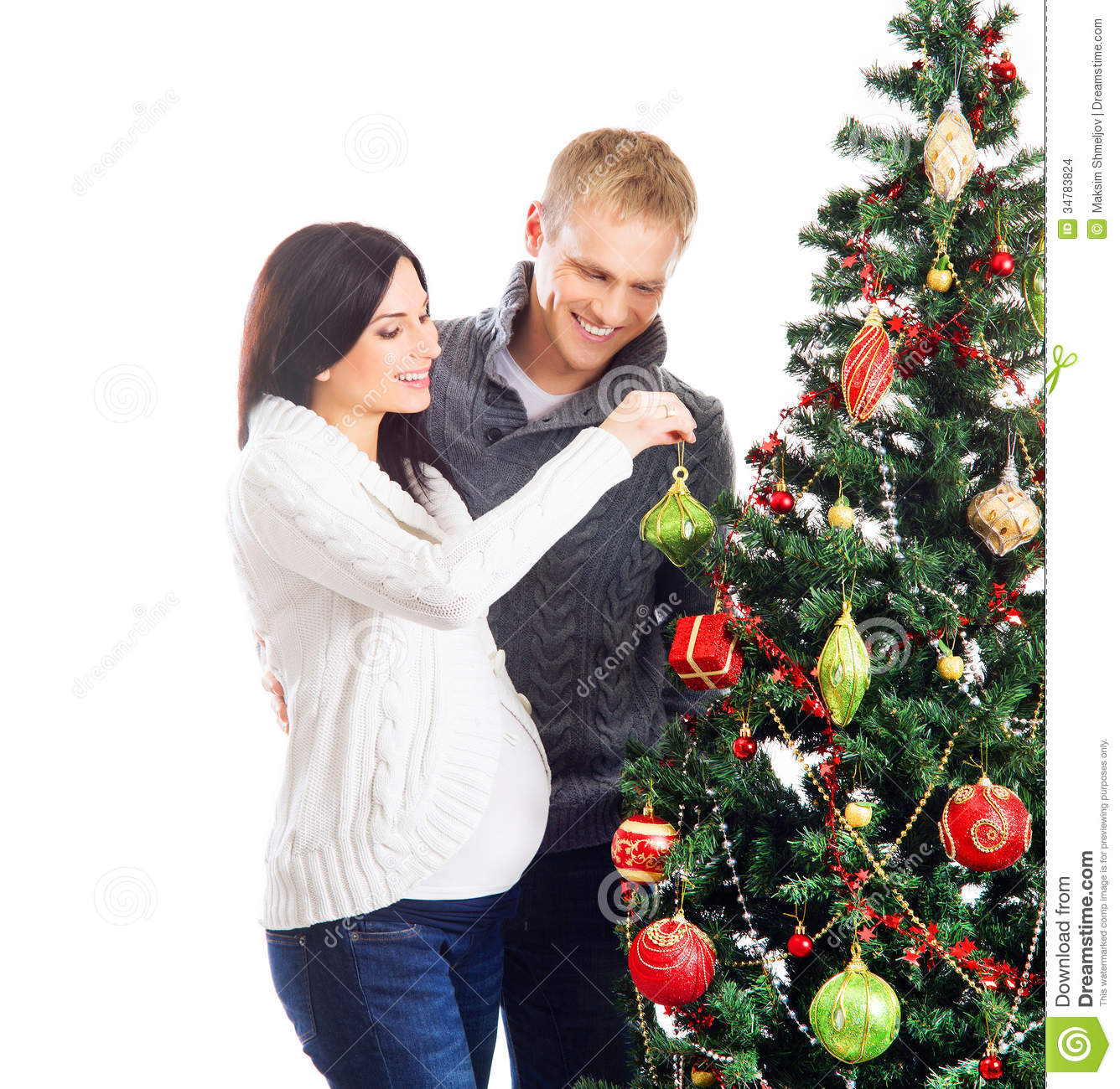 A Couple Waiting For The Baby At Christmas Near The Tree