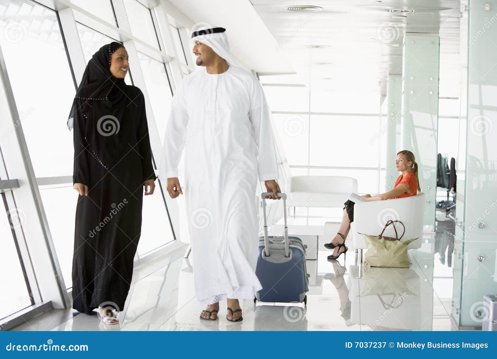 Couple walking through airport departure lounge