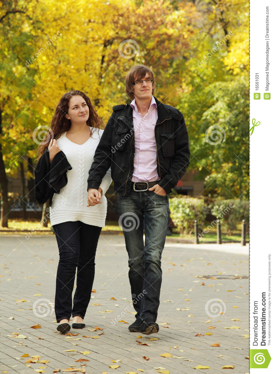 Young couple in casual clothes walking by autumn park Young Couple Walking In The Park