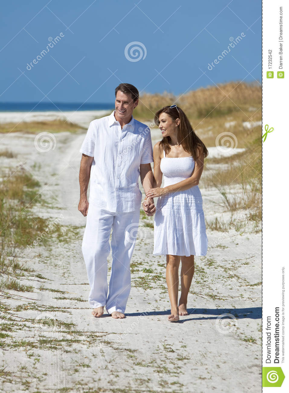567d94514b87 Man and woman romantic couple in white clothes holding hands and walking on  a deserted tropical beach with bright clear blue sky