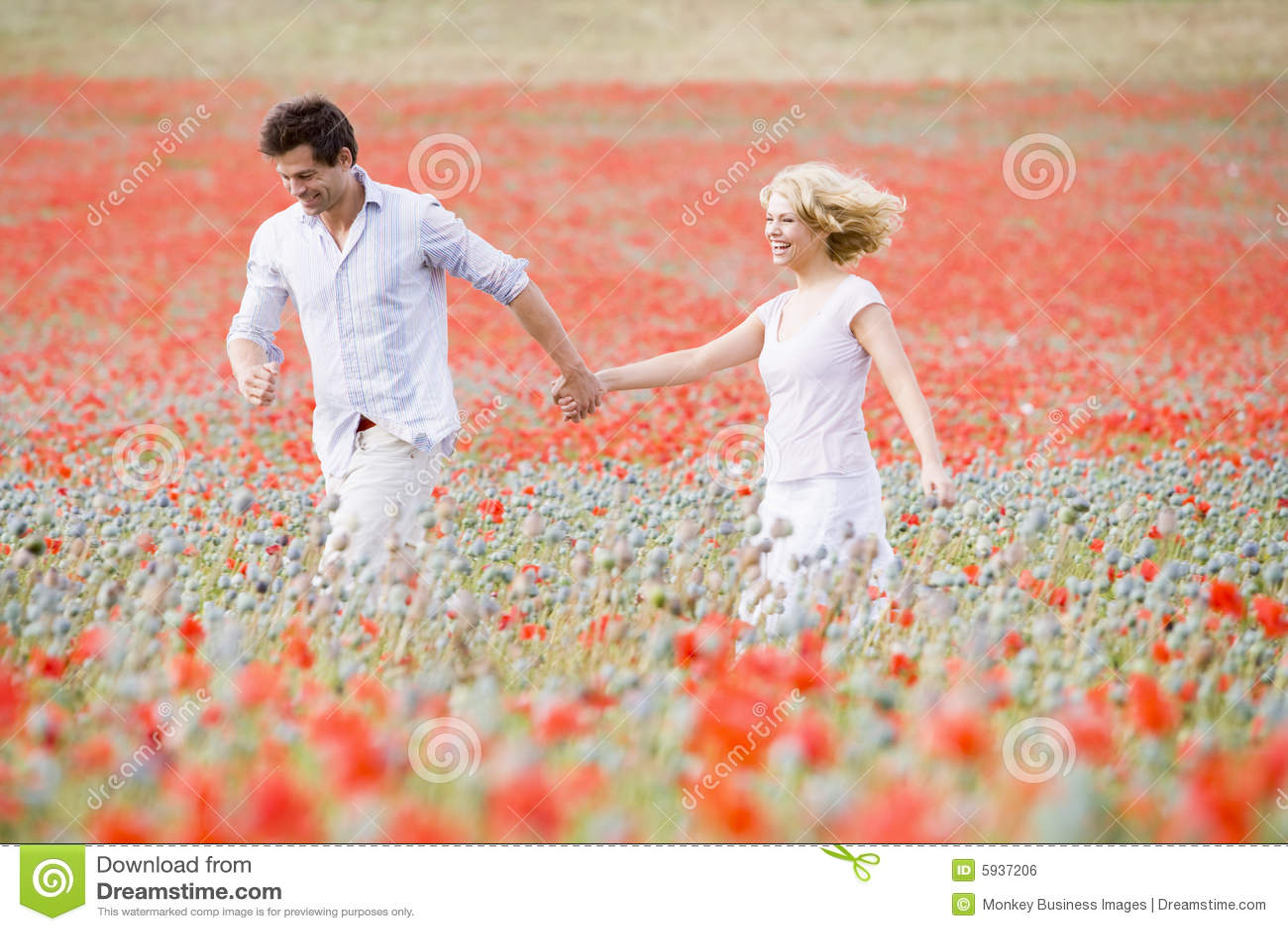 Couple walking in poppy field holding hands