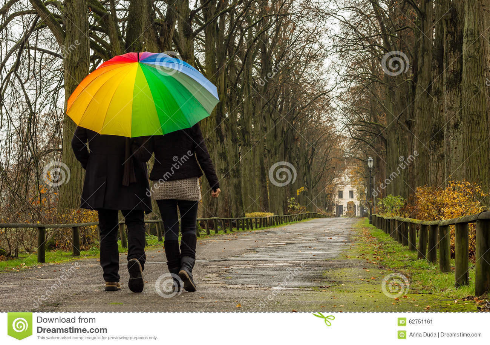 Couple walks under rainbow umbrella