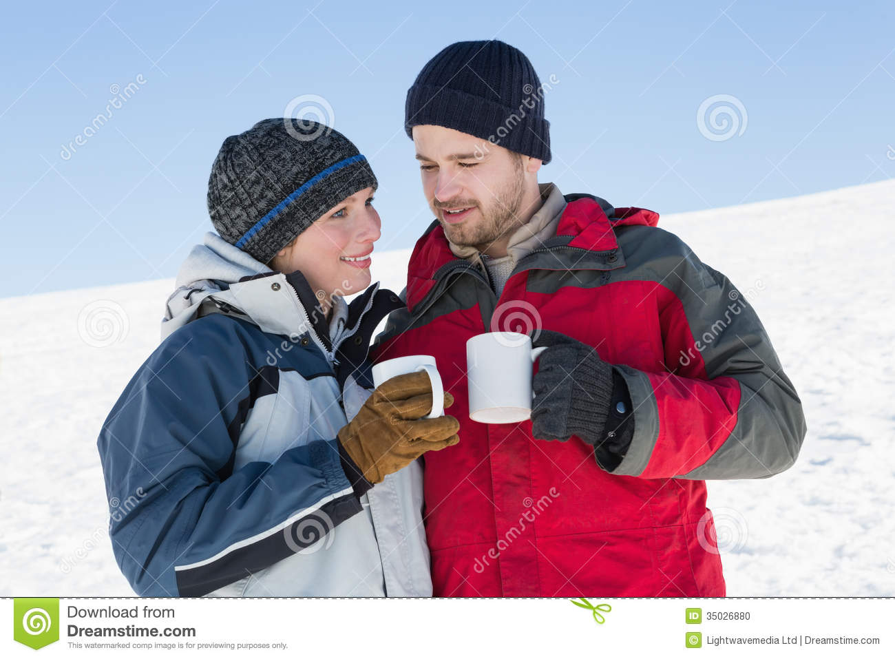 Couple In Warm Clothing With Coffee Cups On Snow Stock Photo ...