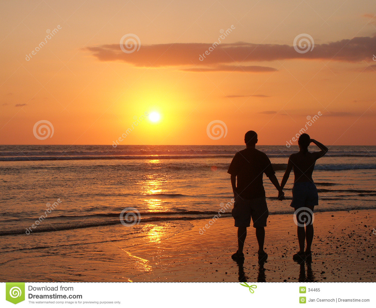 Couple watching the setting sun hand in hand