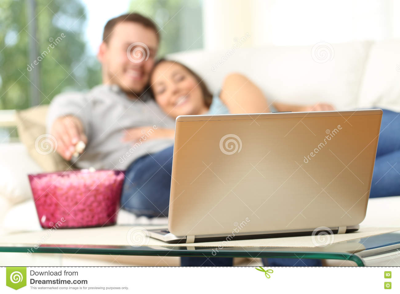 Couple watching tv in a laptop at home
