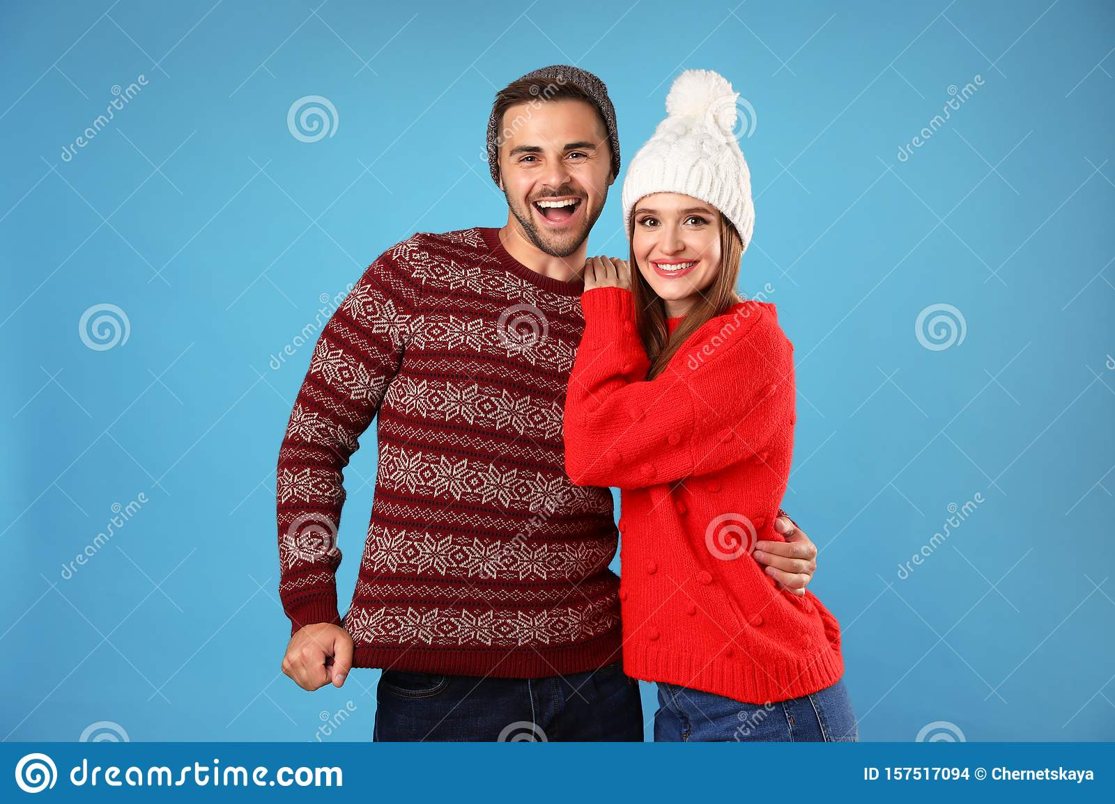 Couple wearing Christmas sweaters and hats on blue