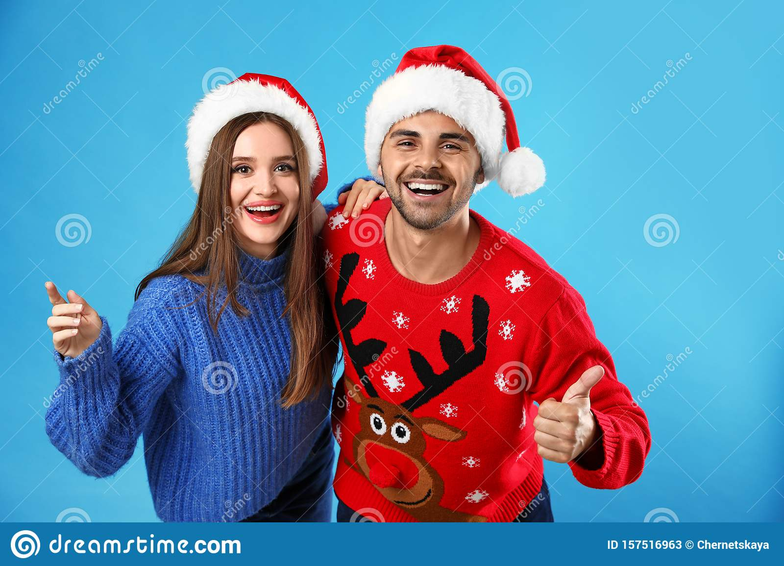 Couple wearing Christmas sweaters and Santa hats