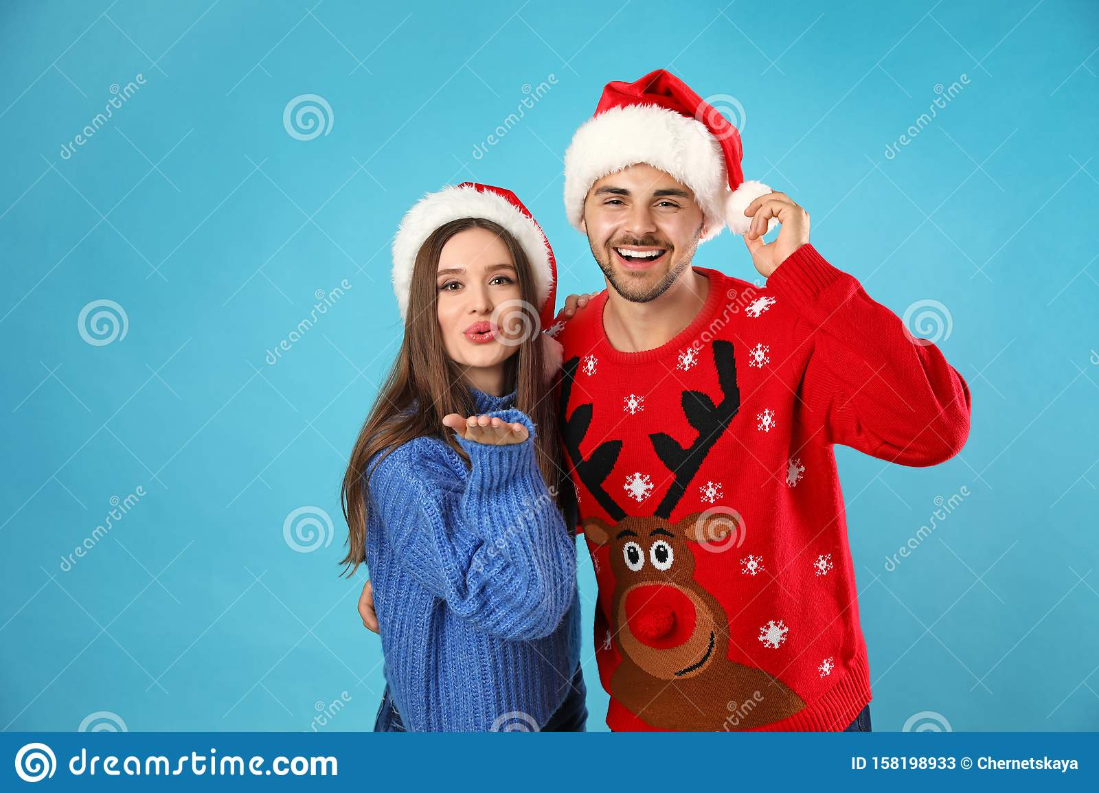Couple wearing Christmas sweaters and Santa hats on background