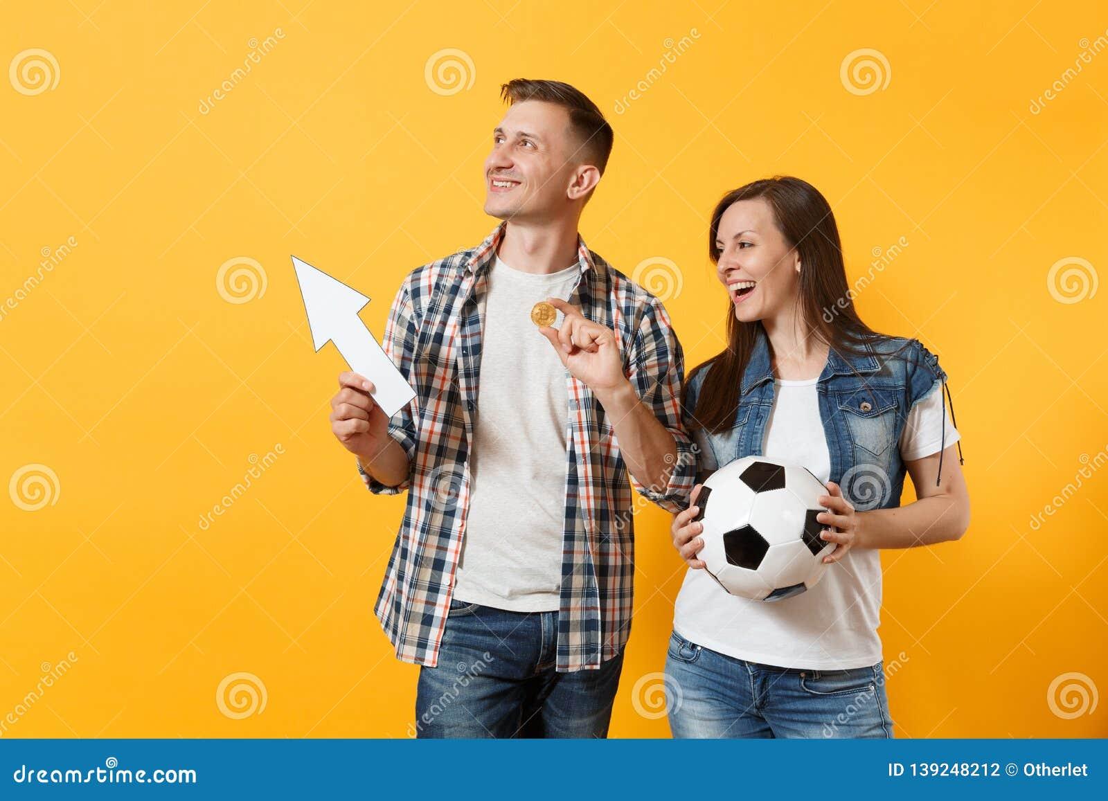 Couple, woman man, football fans holding bitcoin, metal golden coin, up arrow, soccer ball, cheer up support team