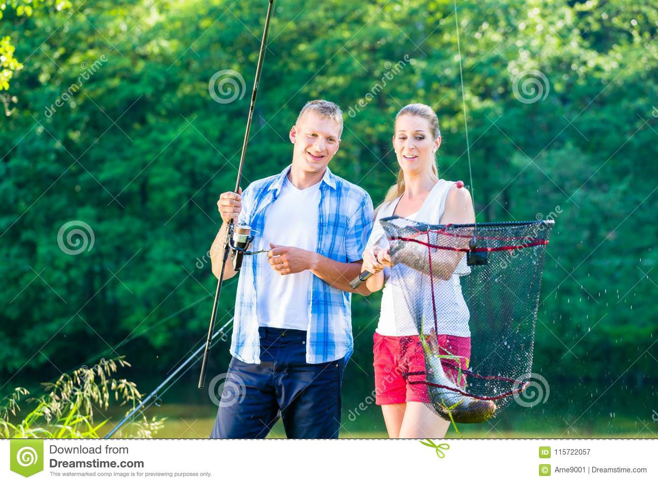 Couple sport fishing bragging with fish caught