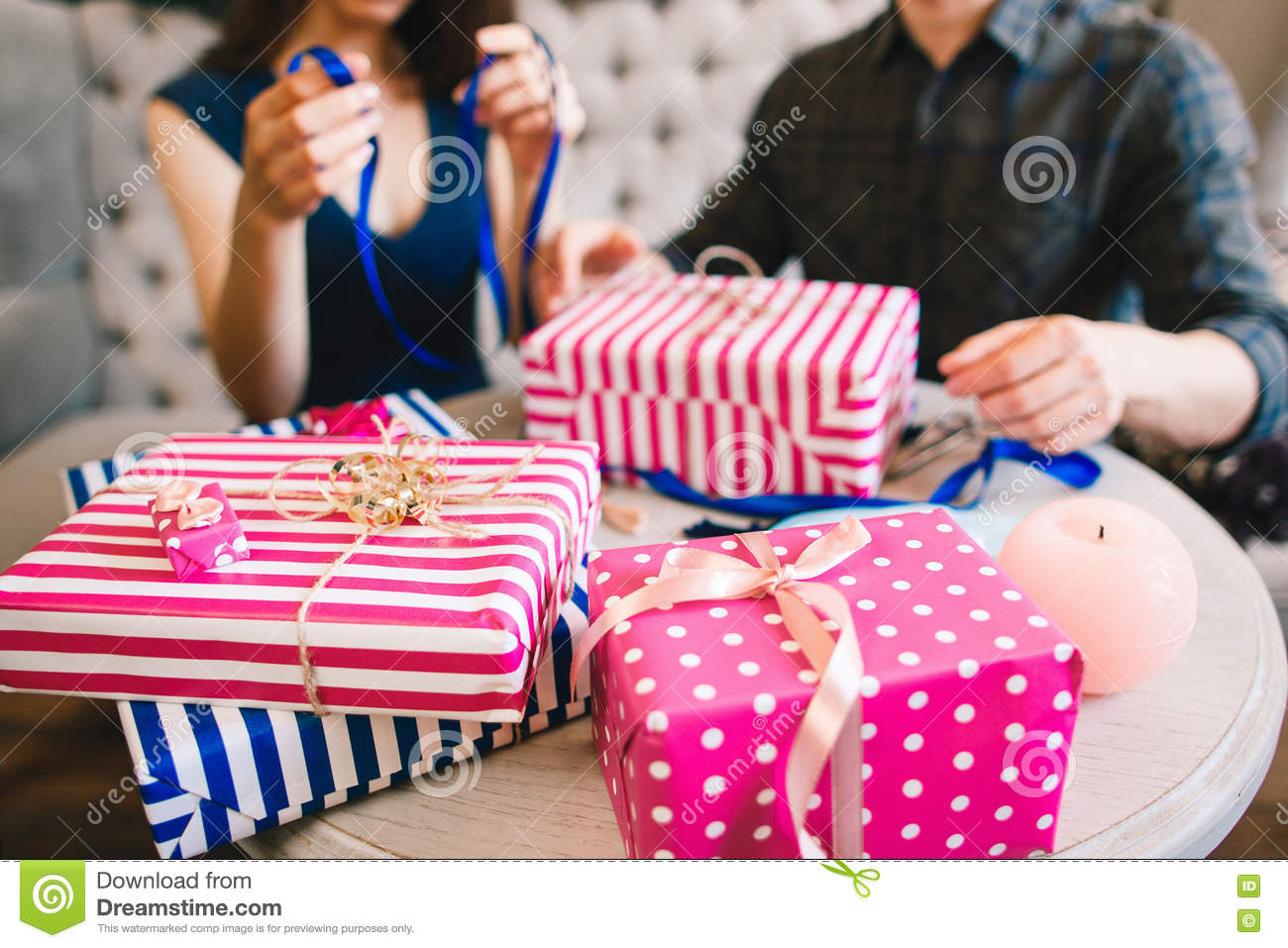 couple wrapping gifts for family and friends focus on bunch of christmas presents on table blurred unrecognizable men and women on background
