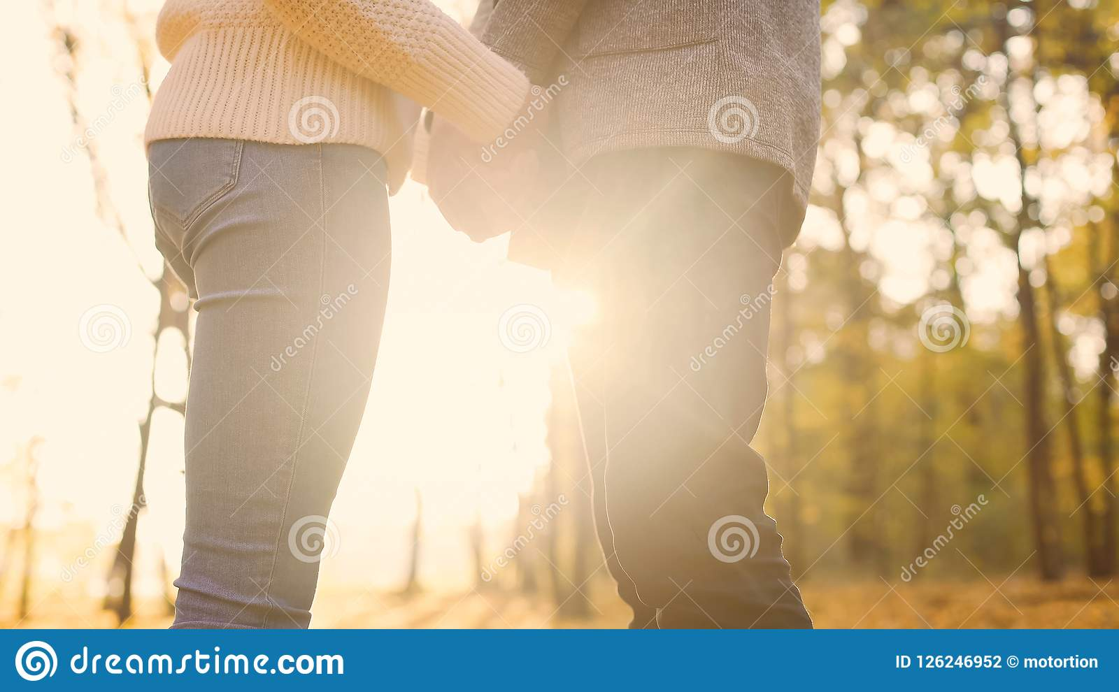 Couple of young lovers tenderly holding hands, enjoying date, warm autumn