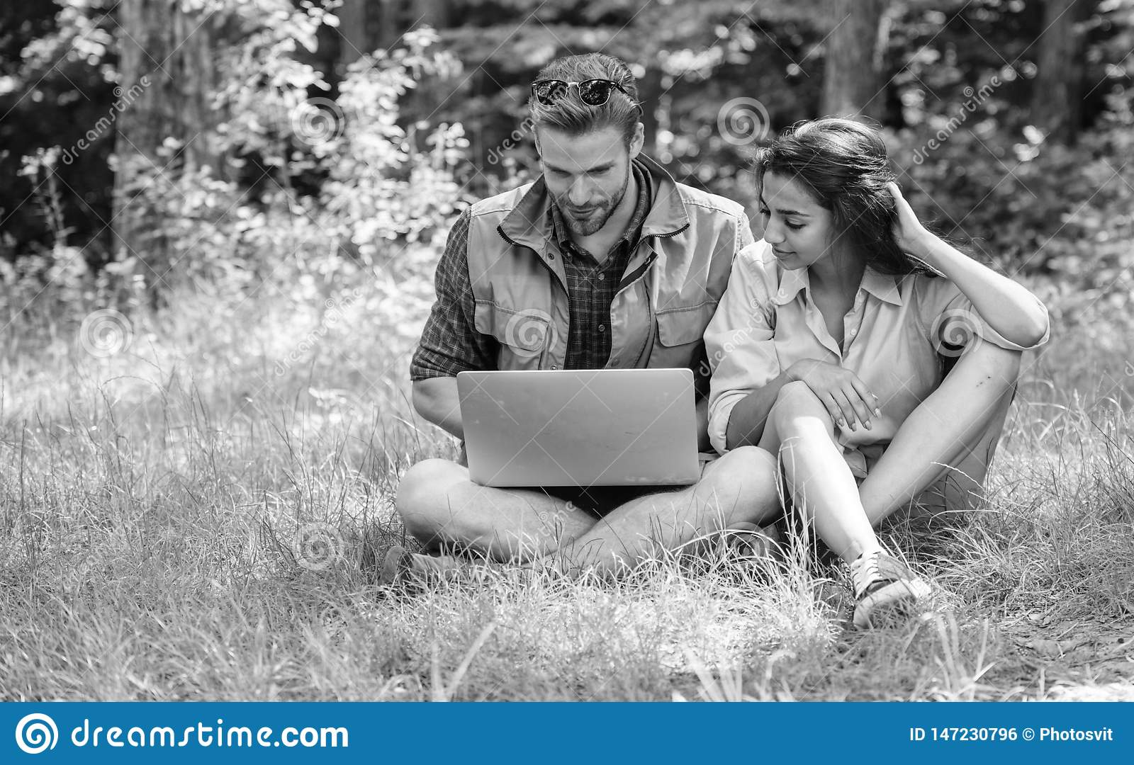 Couple youth spend leisure outdoors with laptop. Man and girl looking at laptop screen. Closer to nature. Modern
