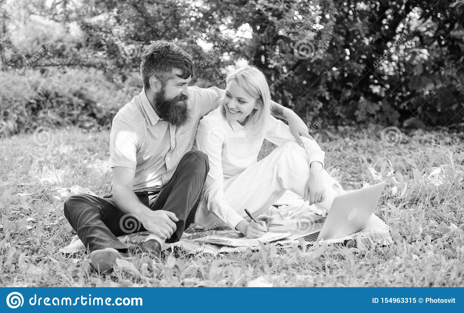 Couple youth spend leisure outdoors working with laptop. Couple in love or family work freelance. Modern online business