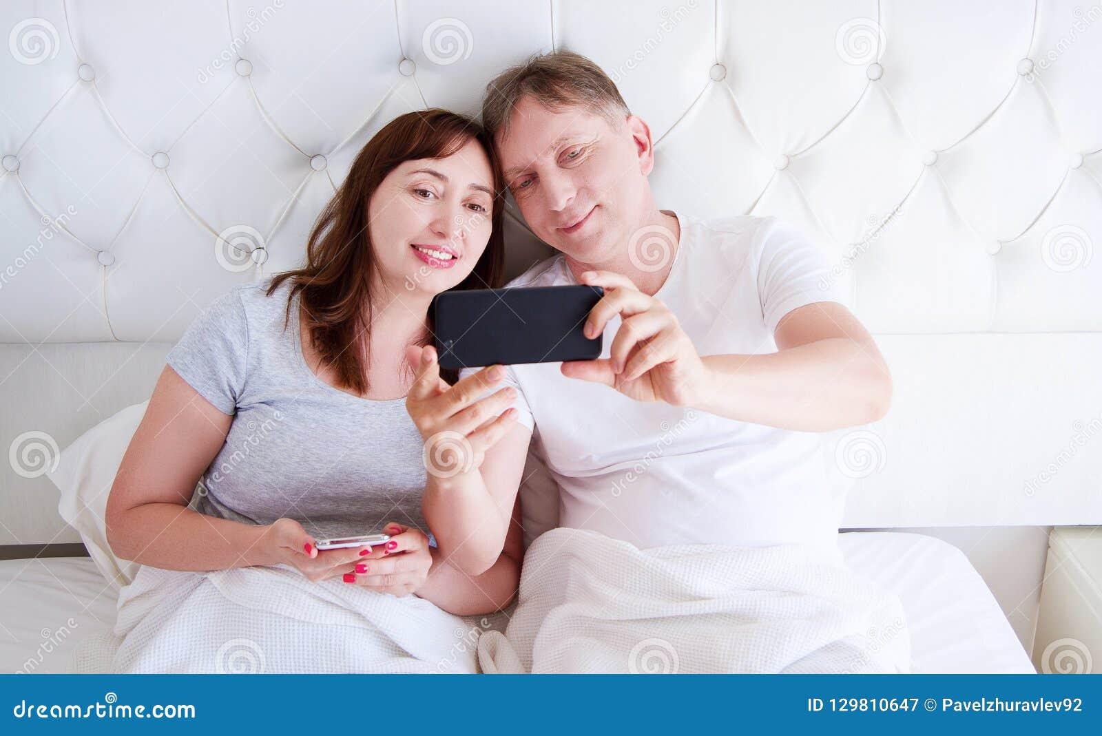 Couples âgés moyens souriant et faire le selfie ou communiquer sur le smartphone dans la chambre à coucher, famille heureuse