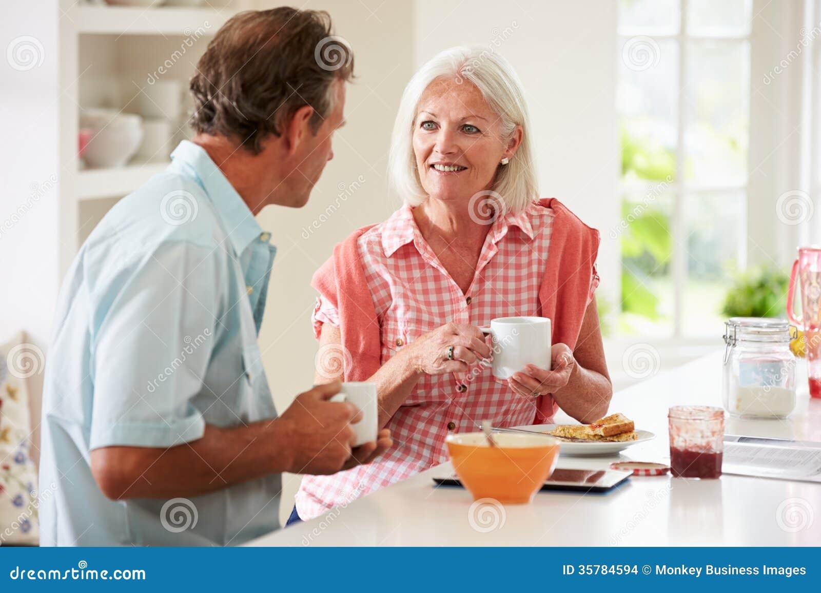 Couples âgés par milieu appréciant le petit déjeuner à la maison ensemble