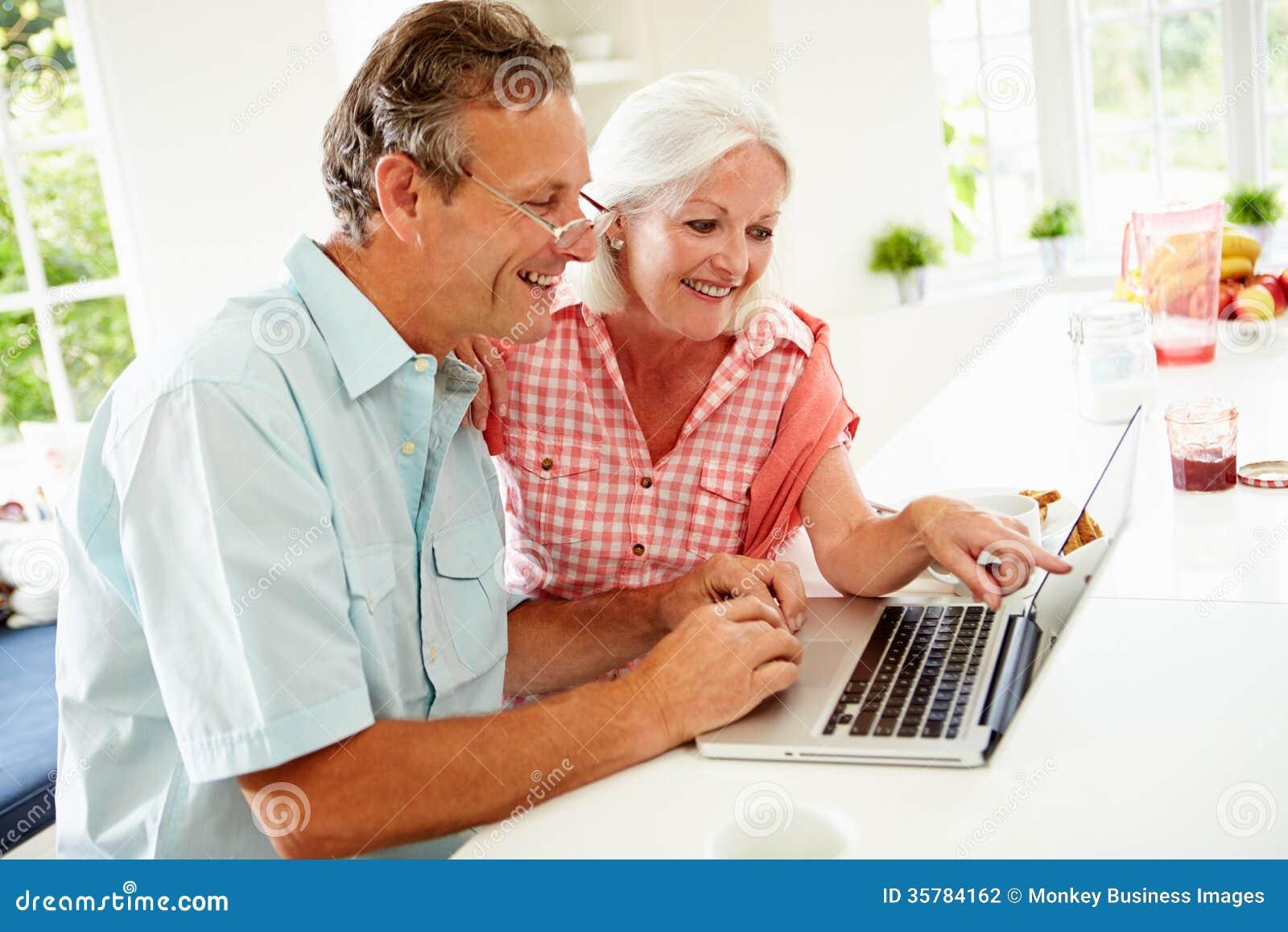 Couples âgés par milieu regardant l ordinateur portable au-dessus du petit déjeuner