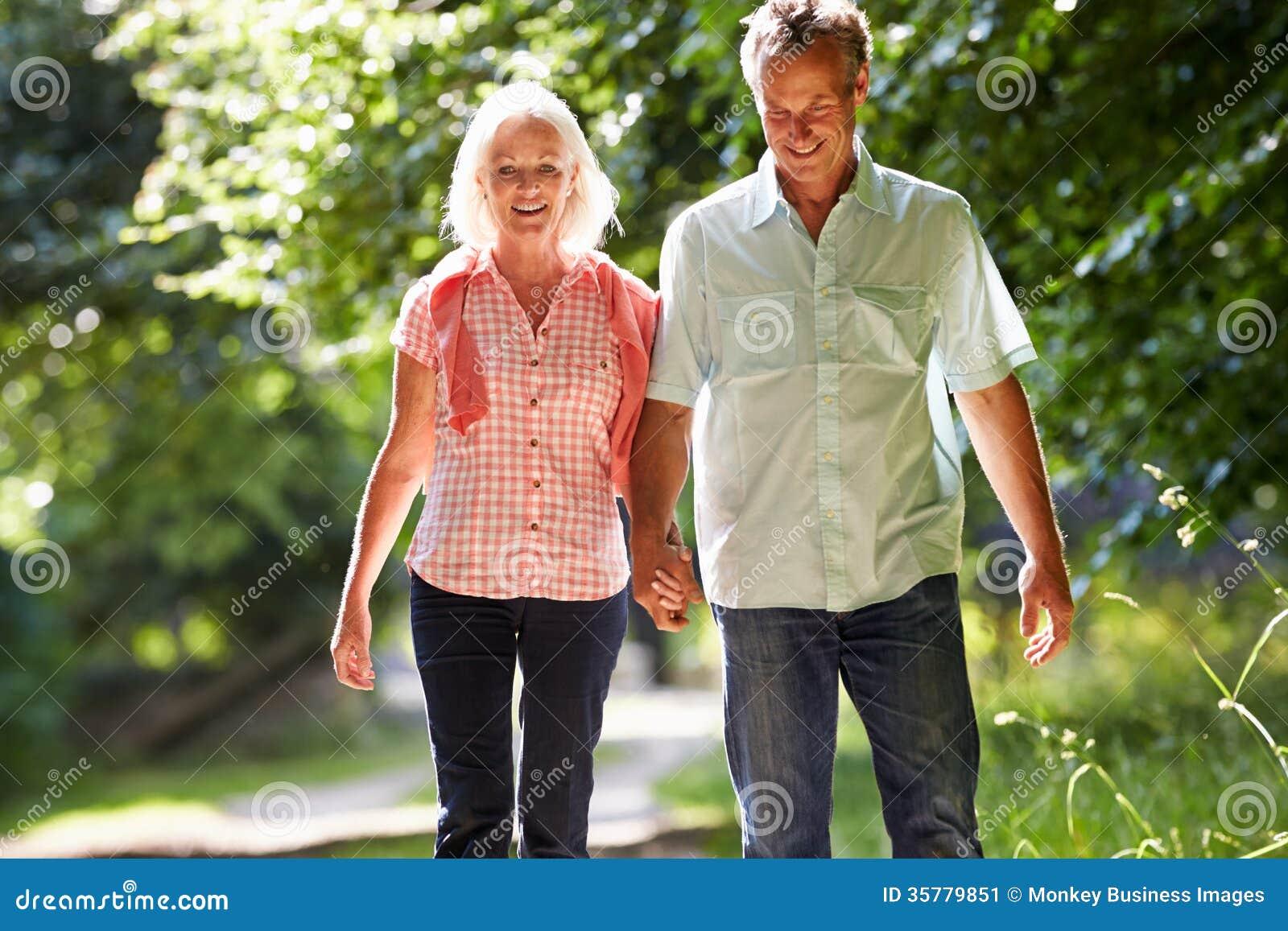 Couples âgés par milieu romantique marchant le long du chemin de campagne