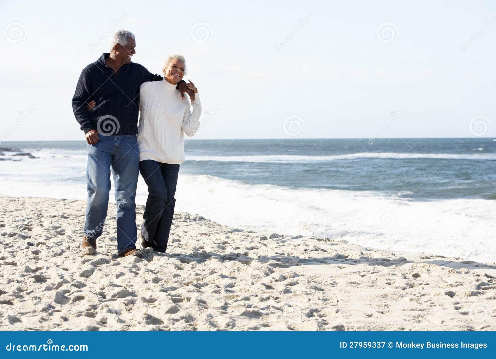 Couples aînés marchant le long de la plage ensemble