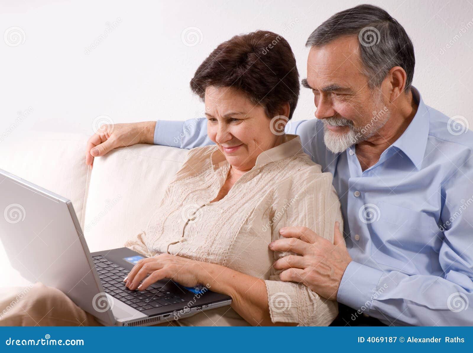 Couples aînés sur l ordinateur portatif